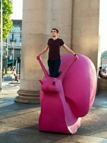 Photo of Greg Kufera atop a sculpture of a pink snail