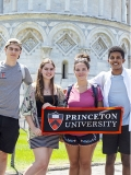 Students holding a banner in front of the tower of Pisa and the Basilica