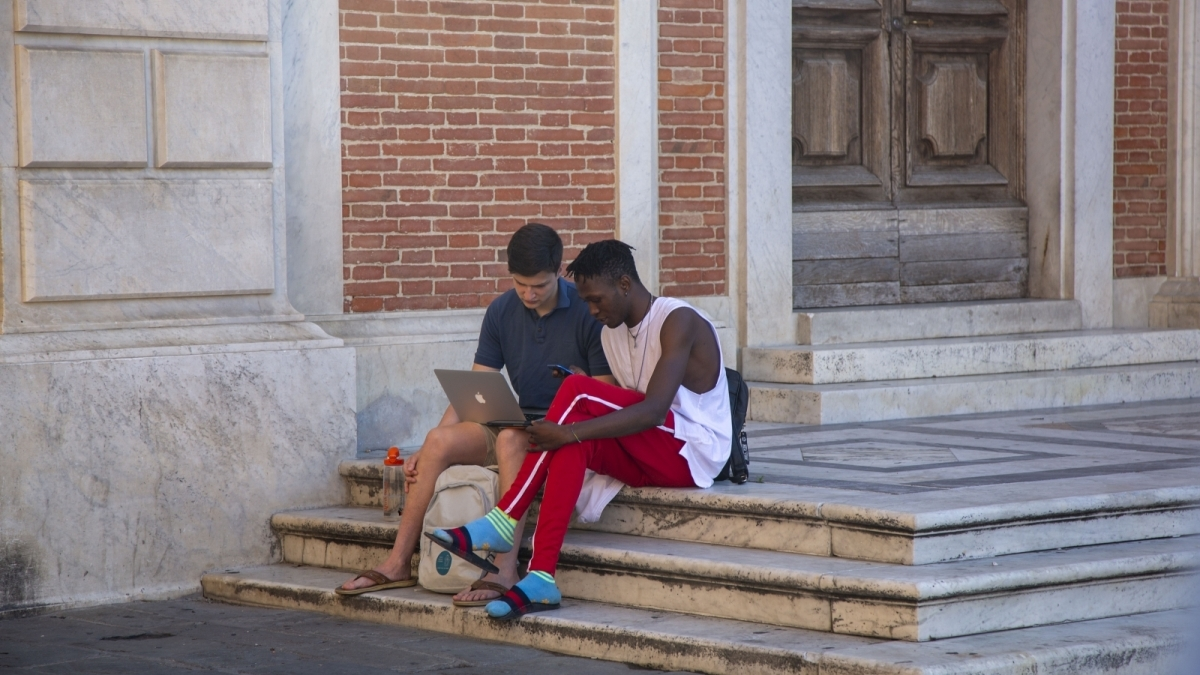 Image of 2 students collaborating while sat on the stairs of the Scuola Normale Superiore in Pisa